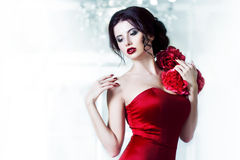 Beauty Brunette model woman in  evening red dress. Beautiful fashion luxury makeup and hairstyle, on the background of Royalty Free Stock Photography