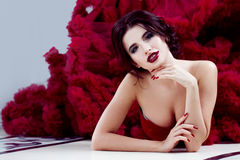 Beauty Brunette model woman in evening red dress. Beautiful fashion luxury makeup and hairstyle stock photography