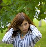 Beauty brunette in a park correct you hairstyle Royalty Free Stock Images