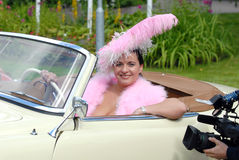 Beauty brunette in pink feathers in retro car Stock Photo