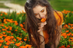 Beauty brunette Romantic Girl Outdoors. Beautiful Teenage Model. Girl smelling flower, over marigold flowers field Royalty Free Stock Images