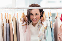 Beauty brunette smiling at camera by clothes rail Royalty Free Stock Images