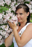 Beauty brunette in summer flowers. Beauty brunette smelling the summer flowers Royalty Free Stock Images
