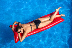 Beauty Brunette Sunbathing in the Pool. Lying on a red mat Stock Image