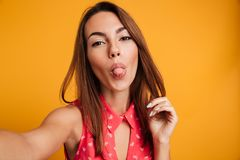 Beauty brunette woman in dress making selfie and showing tongue. At the camera over yellow background Royalty Free Stock Photos