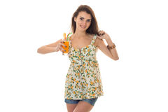 Beauty brunette woman in light sarafan with floral pattern drinks orange cocktail and smiling on camera isolated on Stock Image