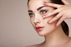 Beauty brunette woman with perfect makeup. Red lips and nails. Perfect eyebrows. Skin care foundation. Beauty girls face isolated on beige background. Fashion royalty free stock image