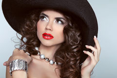 Beauty brunette woman with red lips, wavy hair, fashion jewelry. Royalty Free Stock Photo