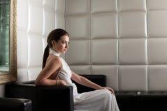 Beauty brunette woman on sofa in nightclub Stock Image