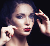 Beauty brunette woman under black veil with red manicure close u Stock Images
