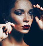 Beauty brunette woman under black veil with red manicure close up Stock Photo