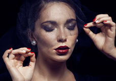 Beauty brunette woman under black veil with red manicure close up, grieving widow, halloween makeup luxury Royalty Free Stock Photography