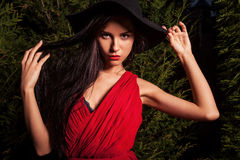 Beauty brunette women in red dress & hat pose at night park. Stock Photography