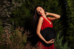 Beauty brunette women in red dress & hat pose at night park. Royalty Free Stock Photos
