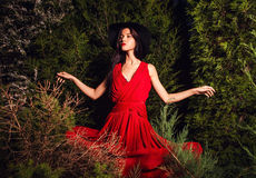 Beauty brunette women in red dress & hat pose at night park. Stock Photo