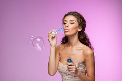 Beauty with bubble wand. Beautiful young women blowing into the Royalty Free Stock Image