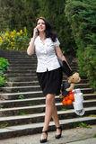 Modern business woman, shopping, phone. Happy elegant woman walking through the park to house, business dressed, talking, smiling, mobile phone. In hands royalty free stock images