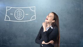Beauty business woman standing near btc logo. Succesful Bitcoin investment. Concept of virtual criptocurrency. stock photo