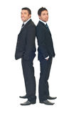 Beauty businessmen in black suits. Full length of two beauty businessmen wearing black suits and standing back to back with hands in pockets suit isolated on Stock Image