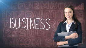 Beauty businesswoman on painted background with marketing words. Advertising, investment and business plan concept. Beauty businesswoman in suit on painted royalty free stock photo
