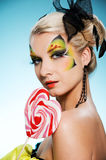 Beauty with butterfly face-art. Young beauty with butterfly face-art heart shaped lollypop Royalty Free Stock Photos