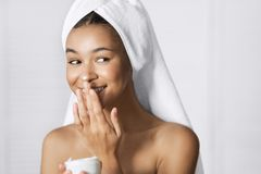 Beauty and care concept. Beautiful afro-american girl applying cream on her face. Beauty and care concept royalty free stock image