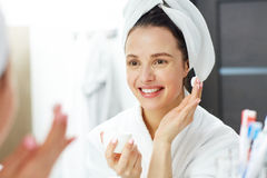 Beauty care. Smiling girl with towel on head going to apply face cream Stock Photography