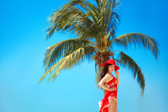 Beauty Carefree young girl with red hat relaxing on tropical bea Royalty Free Stock Photography