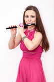 Beauty Caucasian woman flutist playing on small flute, white background Royalty Free Stock Photos