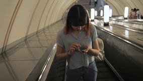 Woman Rise Up At Escalator From Underground Subway And Using Smartphone Apps. Beauty caucasian young brunette woman. Stands on escalator, which rises up from the stock footage