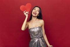 Beauty cheerful Young fashion model Girl with big Valentine Heart in hands. Love Holiday celebration. Valentines Day symbol. Red background royalty free stock images