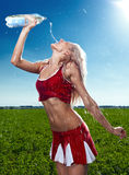 Beauty cheerleader. On field under blue sky Royalty Free Stock Images