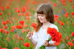 Beauty child portrait at the wild red poppy flowers Stock Images