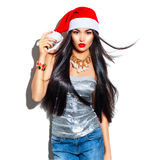 Beauty Christmas fashion model girl with long hair in red santa hat. Beauty Christmas fashion model girl with long straight flying hair in red santa hat Royalty Free Stock Photos