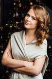 Beauty Christmas fashion model girl. Xmas tree background Royalty Free Stock Photography