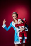 Beauty christmas girl play with baby santa claus Royalty Free Stock Image