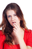 Beauty with cigarette. Beautiful caucasian women in red dress with a cigarette in teeth Stock Photography