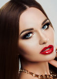 Beauty close-up portrait of young woman with bright makeup, blue eyes and red plump lips. Makeup, beauty, gold. Jewelry Stock Images