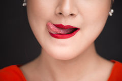 Beauty. Close up view of beautiful woman lips with red matt lips. Tick evincing her desire Stock Image