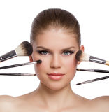 Beauty close-up of young gorgeous blond woman with makeup brushes near her face Stock Image