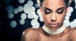 Beauty closeup portrait of elegant woman. Beauty photo of young elegant african american woman . Girl wearing pearls. Glamour makeup. Studio shot Stock Photo