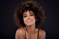 Beauty closeup portrait of girl with afro. Beauty photo of young african american woman with afro. Girl smiling. Glamour makeup. Studio shot Stock Photos