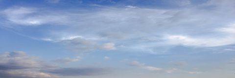 Beauty cloud against a blue sky background. Sky slouds. Blue sky with cloudy weather, nature cloud. White clouds, blue sky and sun. Beauty cloud against a blue stock photography