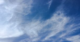 Beauty cloud against a blue sky background. Sky slouds. Blue sky with cloudy weather, nature cloud. White clouds, blue sky and sun. Beauty cloud against a blue stock photo