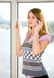 Beauty communication. Blonde is speaking by mobile phone near window; sunlight Stock Photo