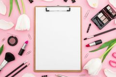 Beauty composition with clipboard, tulips flowers, cosmetics and accessory on pink background. Top view. Flat lay. Home feminine d. Beauty composition with royalty free stock images