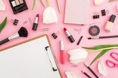 Beauty composition with clipboard, tulips flowers, cosmetics and accessory on pink background. Top view. Flat lay. Home feminine d. Beauty composition with royalty free stock photos