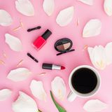 Beauty composition with tulips flowers, coffee mug and cosmetics on pink background. Top view. Flat lay. Home feminine desk. Beauty composition with tulips royalty free stock photography