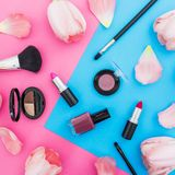 Beauty composition with tulips flowers and cosmetics on bright background. Top view. Flat lay, home feminine desk. Beauty composition with tulips flowers and royalty free stock images