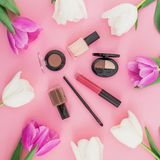 Beauty composition with tulips flowers and cosmetics - lipstick, nail polish on pink background. Top view. Flat lay. Home feminine. Beauty composition with stock photo